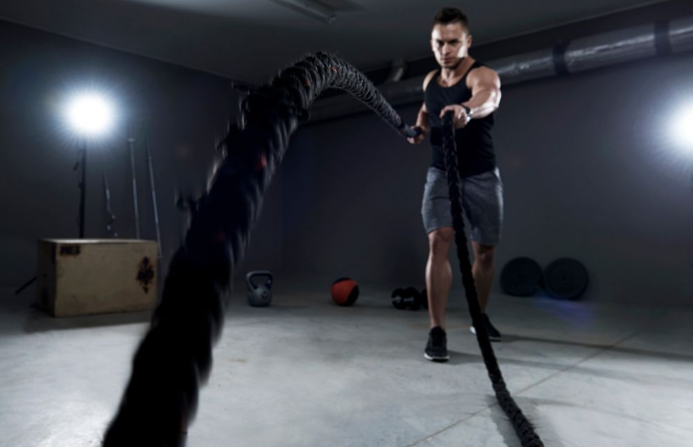 Man exercising with a cord in a gym