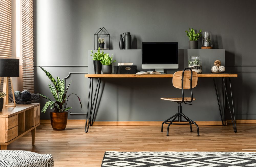 Home office with plants and wooden furniture