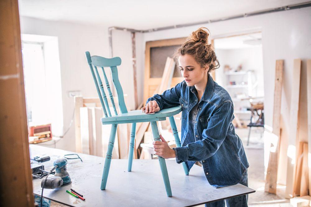 Woman sanding an old chair