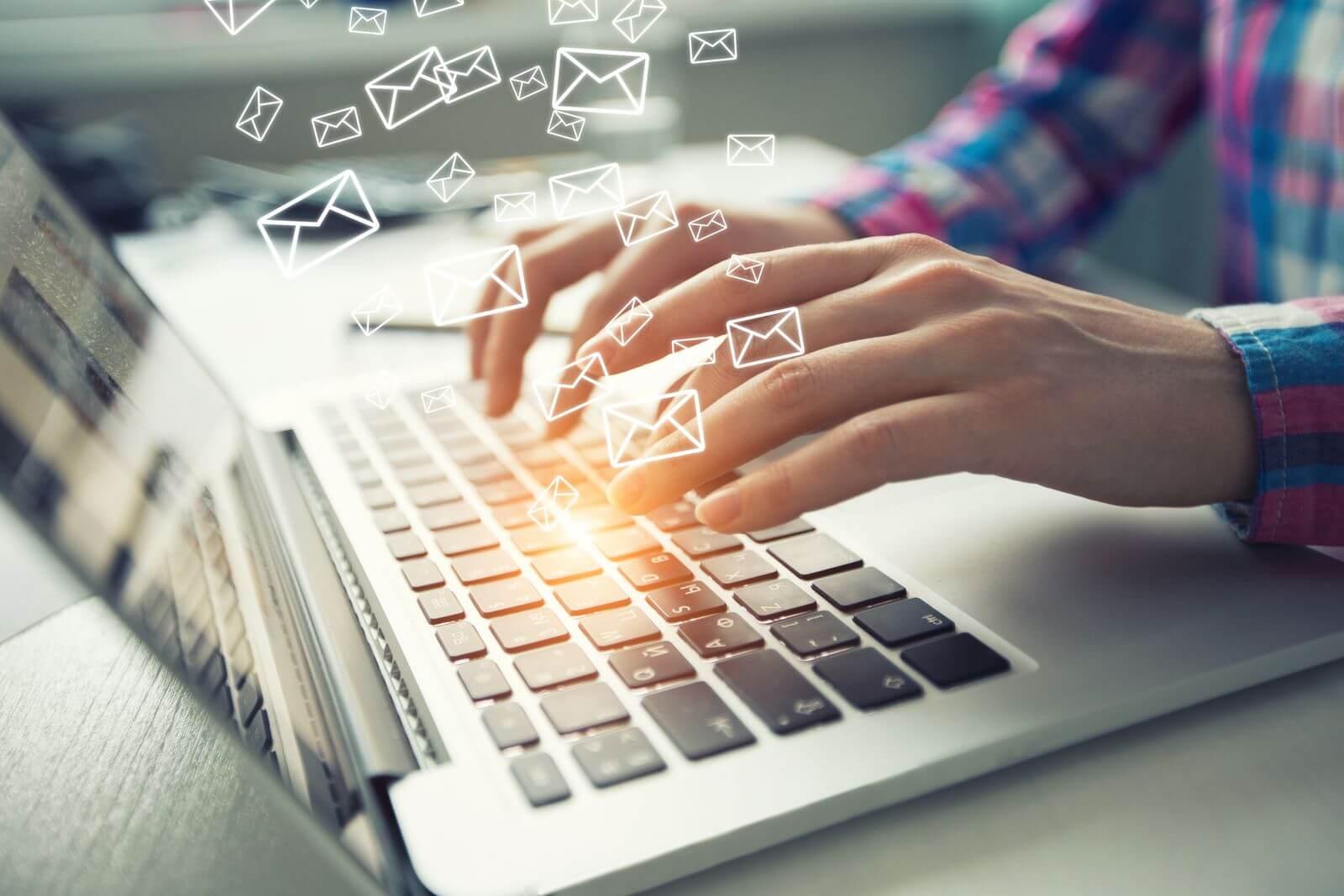 Man sending emails on laptop