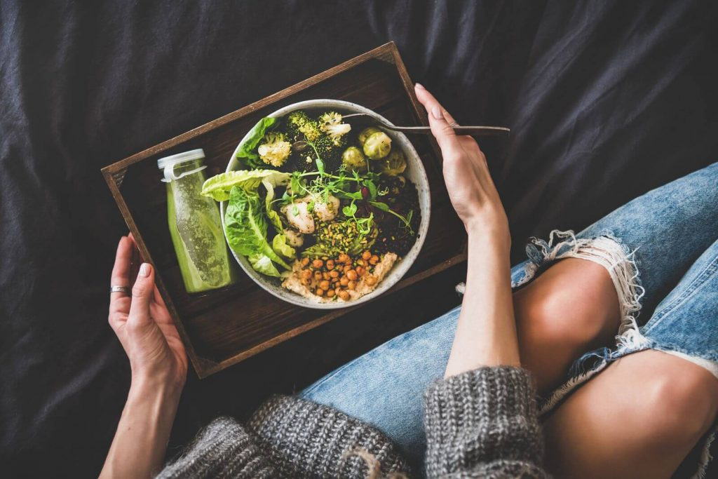 Woman with bowl of healthy greens