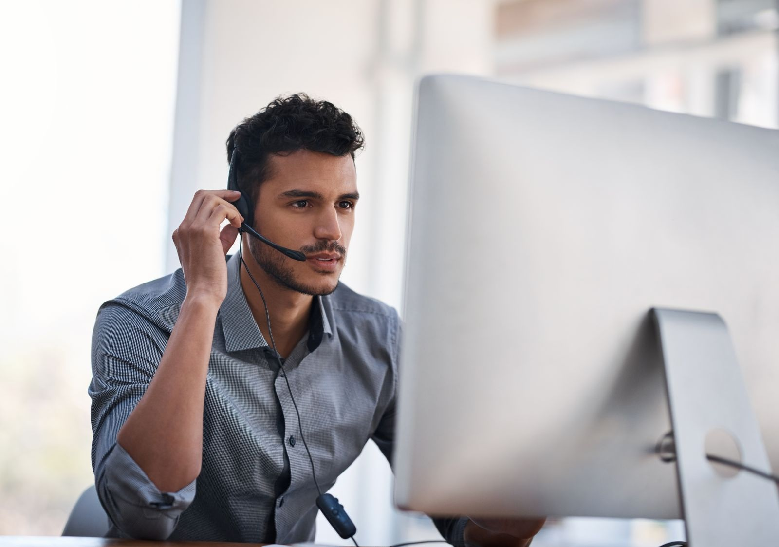 Employee working at computer with headset