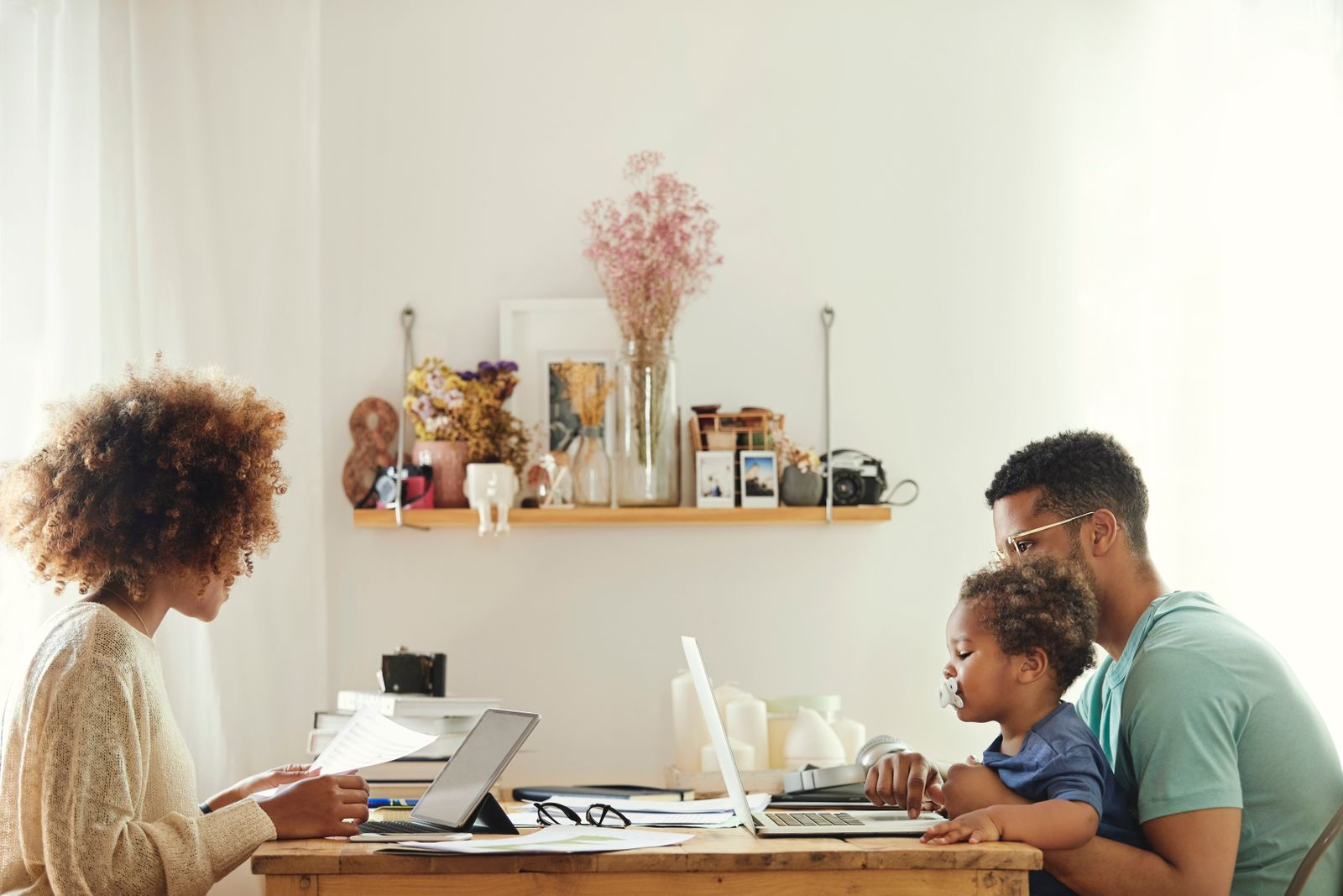 Young couple working from home with their child