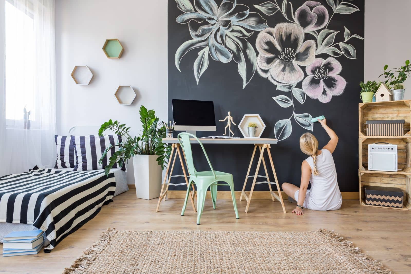 Woman decorating home office chalkboard wall