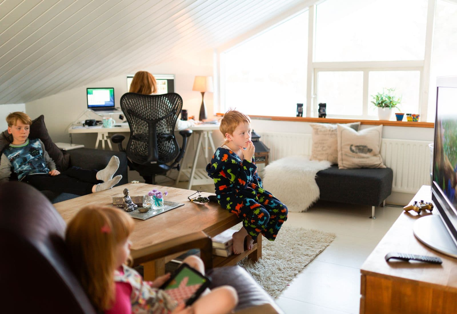 Mother working at home with children