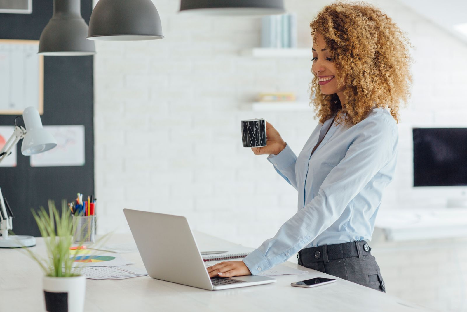 Businesswoman happily using her laptop and holding a mug