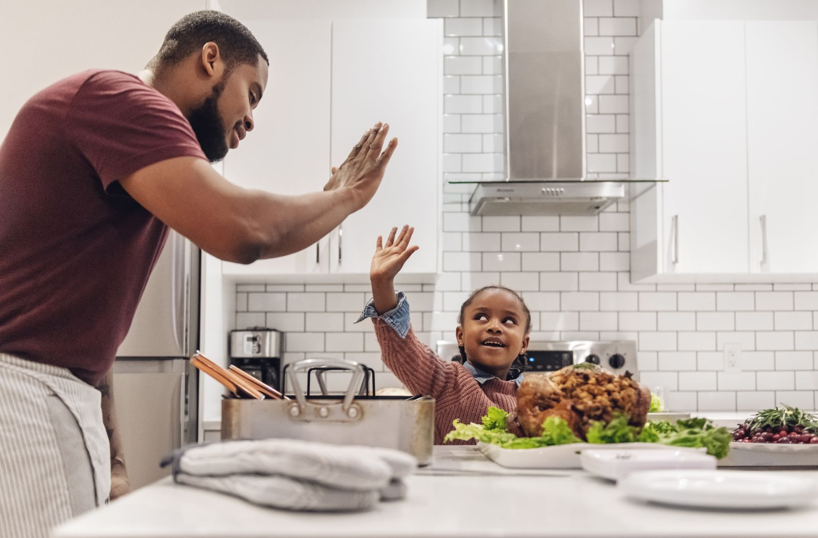Dad cooking Thanksgiving dinner with his daughter