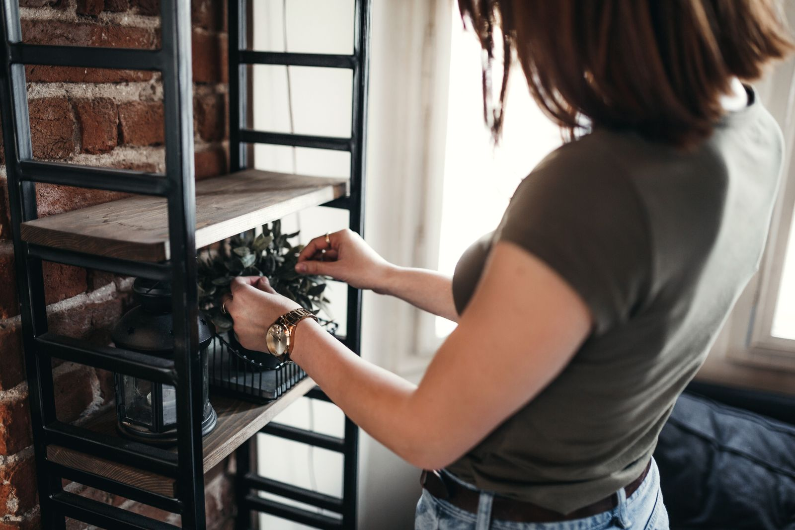 Woman placing a plant on a shelf