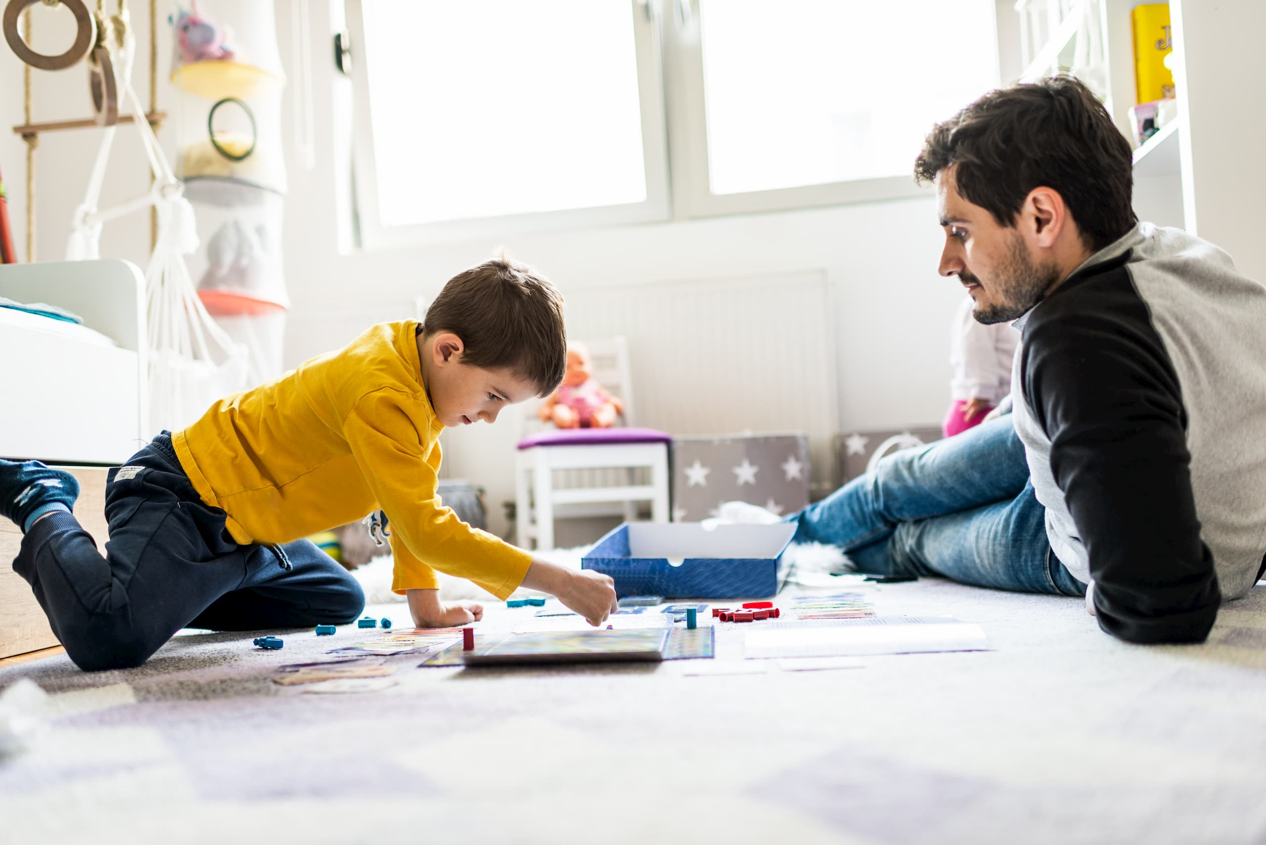 Dad playing with his son in a bright room