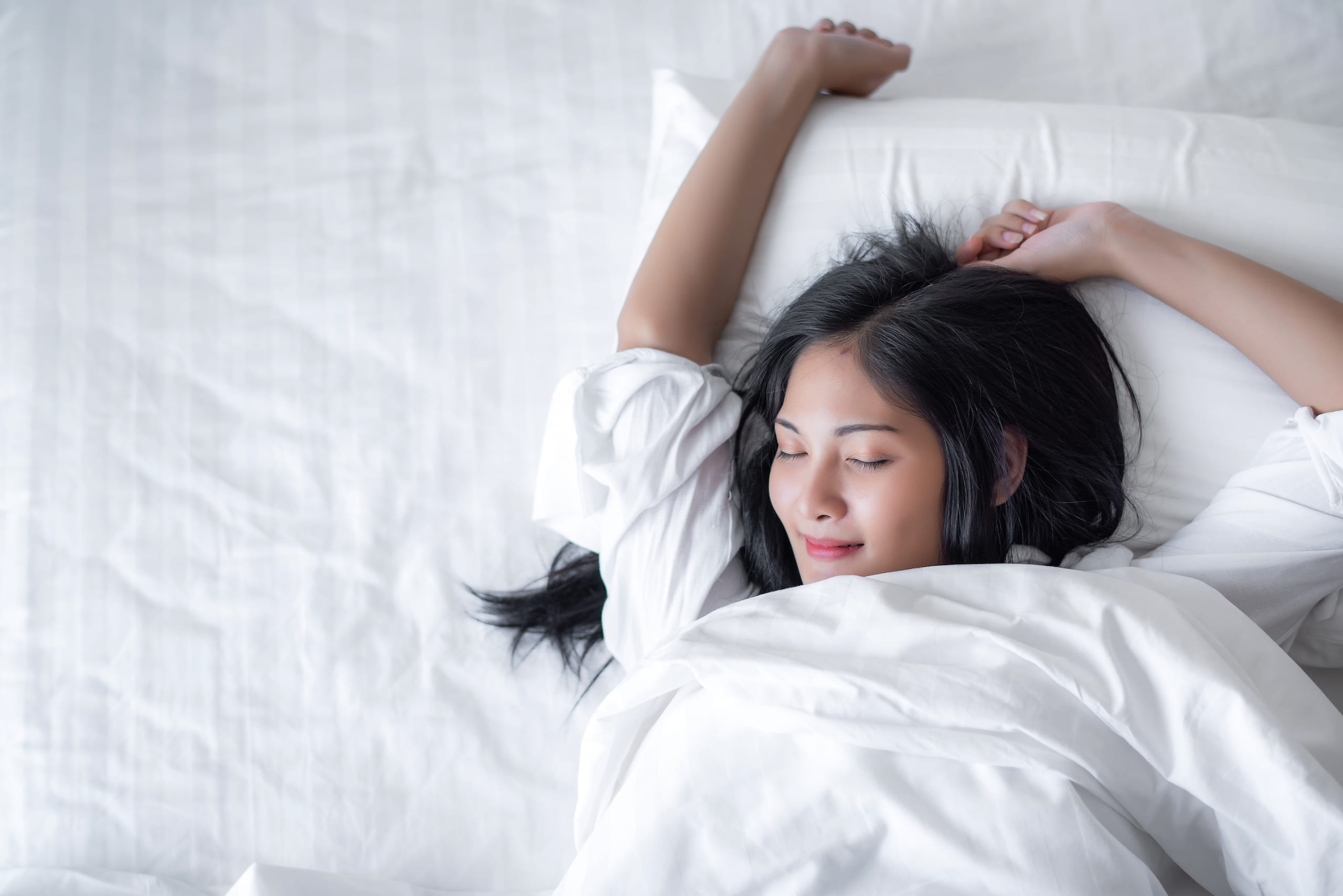 woman stretching in white bed