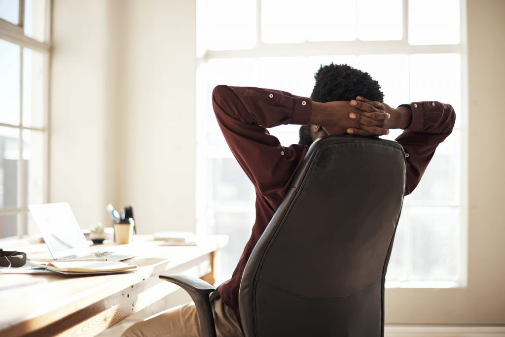 man leaning back in chair with hands behind his head