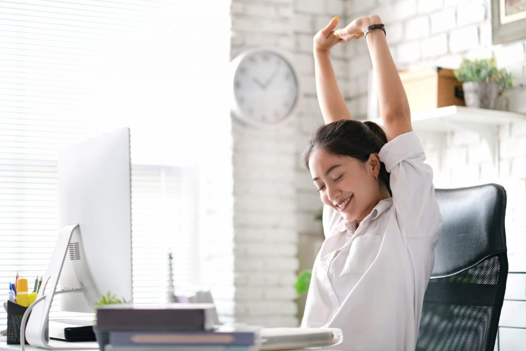 woman stretching with hand up in front of computer