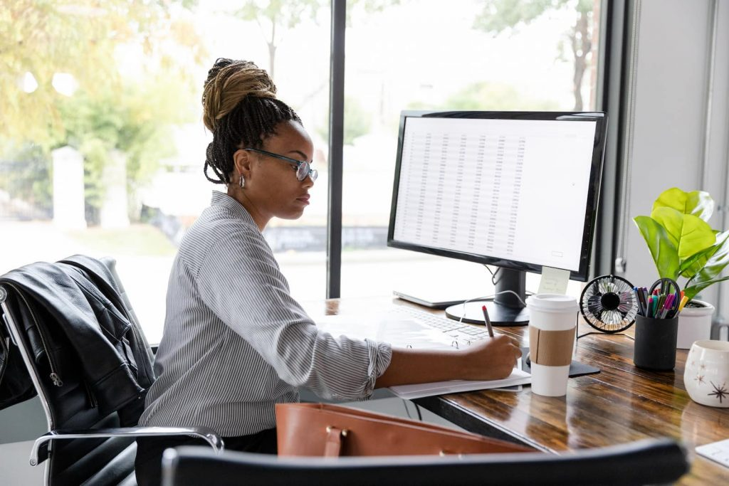 woman writing and working at computer next to big window