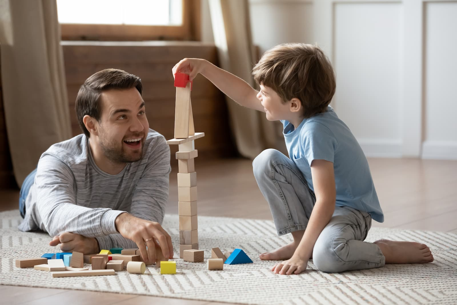 father and son playing together with wooden blocks building pyramids