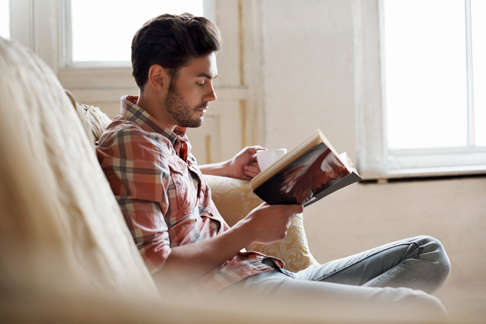 man reading book on the couch with coffee in hand