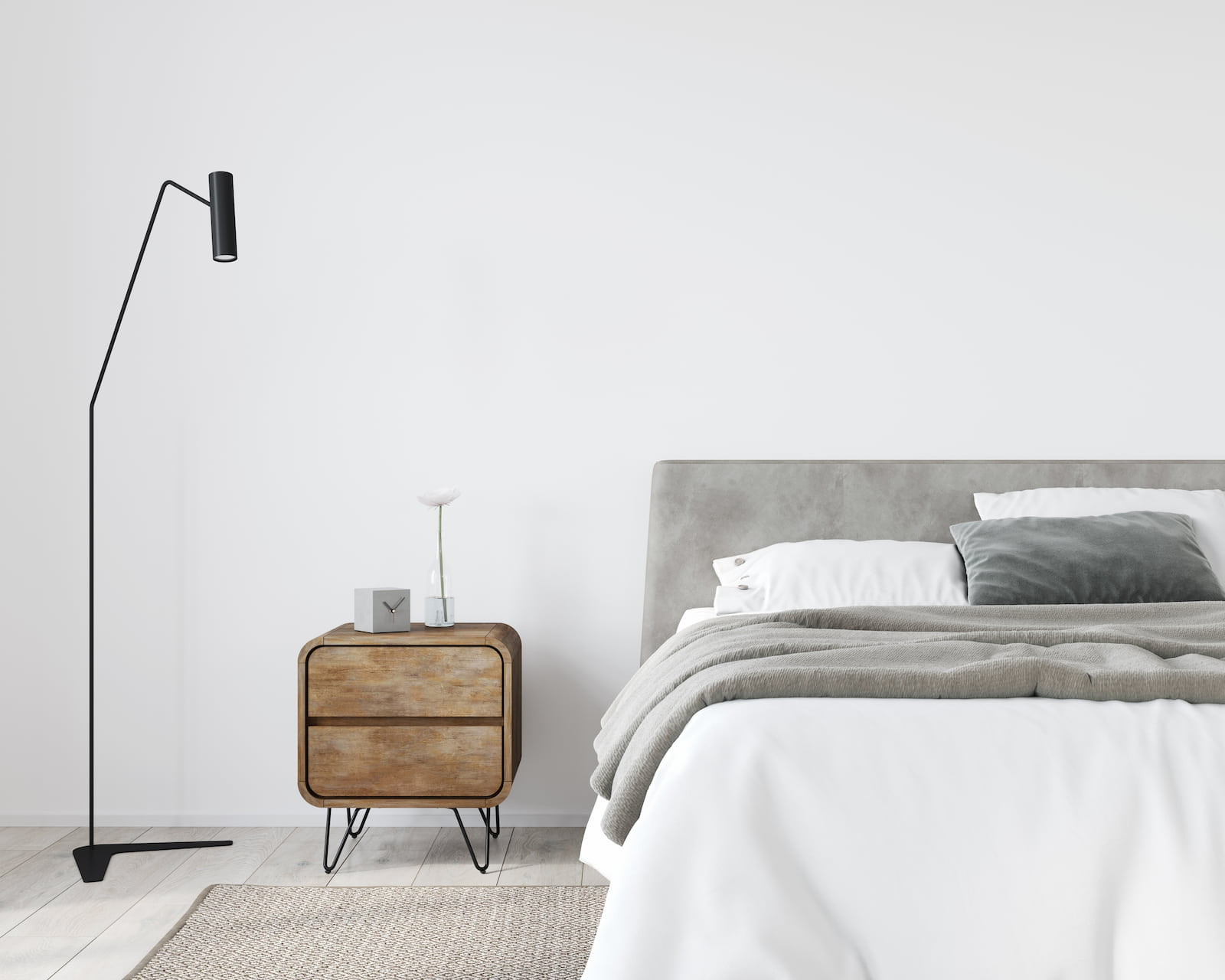 minimalist bedroom with grey bedding and small nightstand and standing light