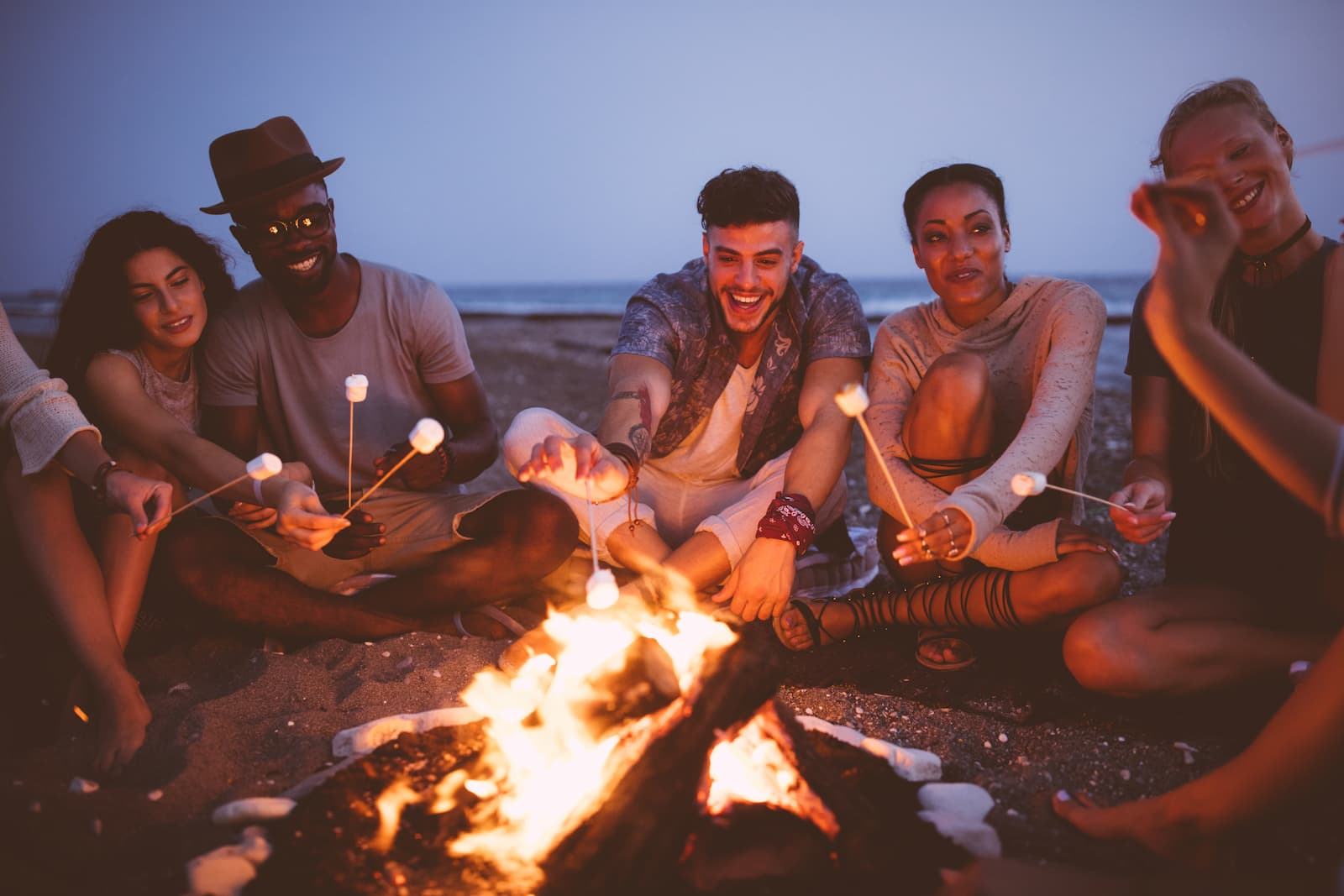friends at a bonfire roasting marshmallows