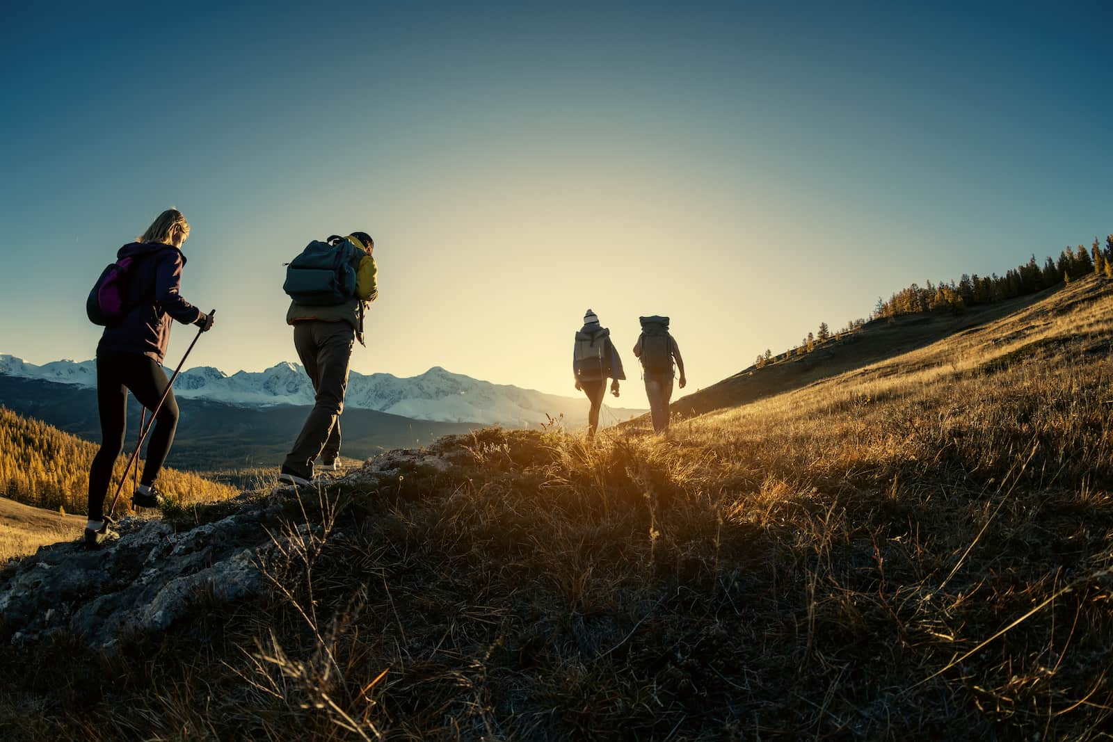 people hiking a mountain at sunset